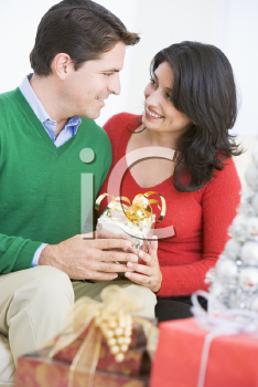 Royalty Free Photo of a Man Giving His Wife a Christmas Gift