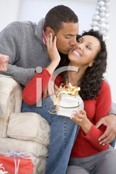 Royalty Free Photo of a Husband Kissing His Wife and Giving Her a Gift