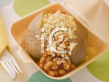 Royalty Free Photo of a Baked Potato With Baked Beans And Cheese In A Take Away Box