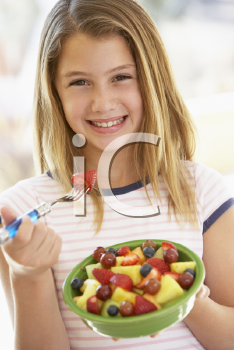 Royalty Free Photo of a Girl Eating Fruit Salad