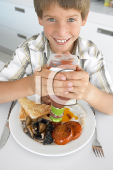 Royalty Free Photo of a Boy Eating Bacon and Eggs With Ketchup
