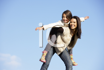 Royalty Free Photo of a Mother Giving Her Daughter a Piggyback Ride