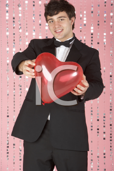 Royalty Free Photo of a Young Man in a Suit Holding a Heart