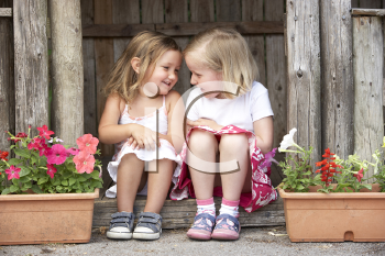 Royalty Free Photo of Two Girls at a Wooden House