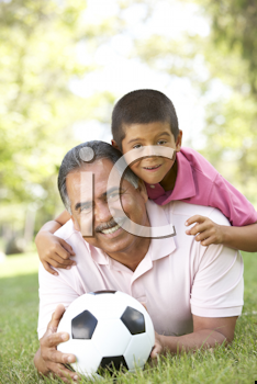 Royalty Free Photo of a Grandfather and Grandson on the Ground With a Soccer Ball