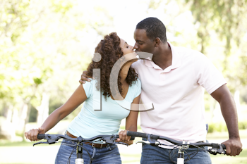 Royalty Free Photo of a Couple on Bikes Kissing