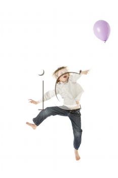 Young Boy Jumping With Balloon In Studio
