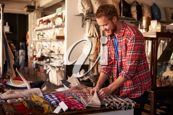 Male Sales Assistant Arranging Textiles In Homeware Store