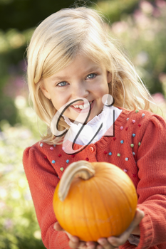 Young girl posing with pumpkin in garden