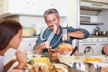 Multi-Generation Family Sitting Around Table Eating Meal