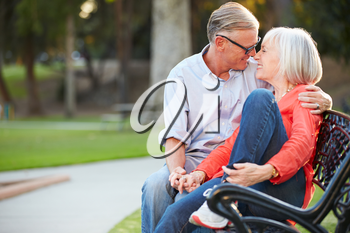 Mature Romantic Couple Sitting On Park Bench Together