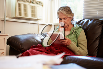 Senior Woman Keeping Warm Under Blanket With Photograph