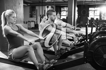Black And White Shot Of Gym Class Using Rowing Machines