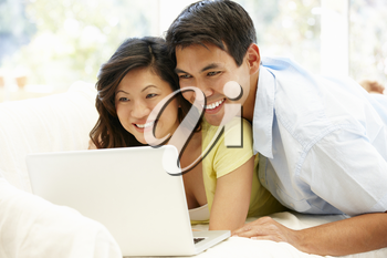 Asian couple using laptop at home