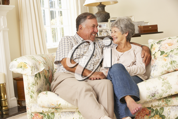 Retired Senior Couple Sitting On Sofa At Home Together