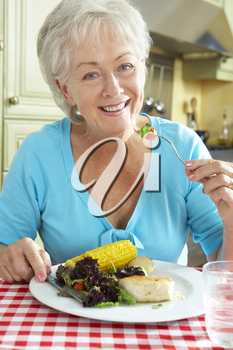 Senior Woman Eating Meal In Kitchen