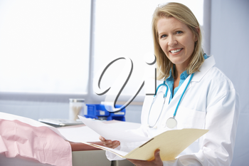 Female Doctor In Surgery Reading Patient Notes