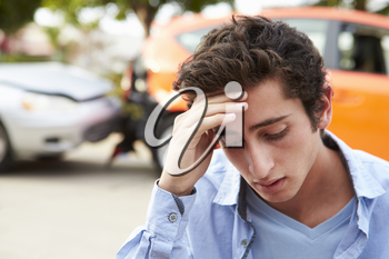Worried Teenage Driver Sitting By Car After Traffic Accident