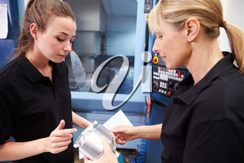 Apprentice Working With Female Engineer On CNC Machinery