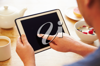 Person Looking At Digital Tablet Whilst Eating Breakfast