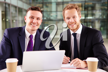 Two young businessmen having coffee, using a laptop computer