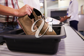Man Putting Shoes Into Tray For Airport Security Check