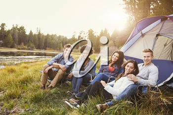 Friends on a camping trip relaxing by a tent look to camera
