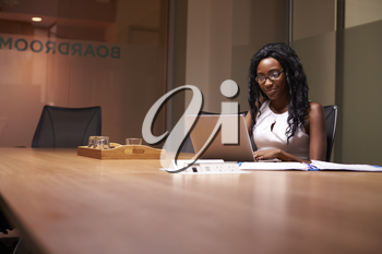 Young black businesswoman working late on laptop in office