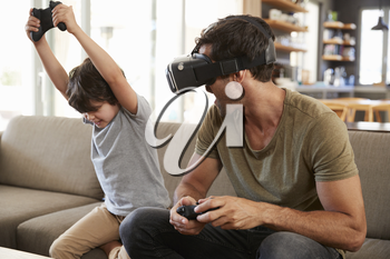 Father And Son Play Computer Game Using Virtual Reality Headset