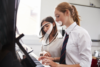 Female Pupil With Teacher Playing Piano In Music Lesson