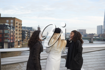 Rear View Of Female Friends Visiting London In Winter