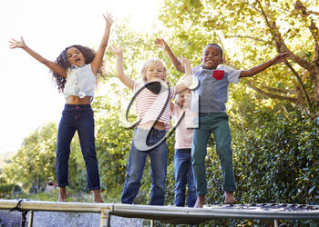Four kids having fun together on a trampoline in the garden