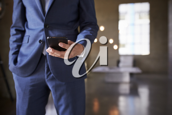 Mid section of man in blue suit using smartphone, close up
