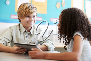 Young girl and boy using tablet in elementary school class