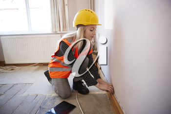 Female Surveyor In Hard Hat And High Visibility Jacket With Digital Tablet Carrying Out House Inspection
