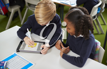 Elevated view of a girl and a boy using a tablet computer and stylus together in a primary school class