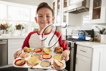 Proud pre-teen Hispanic boy standing in kitchen presenting the cakes he�s made to camera, close up