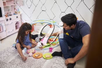 Young girl playing tea party with dad, sitting on the floor, baby brother beside them, elevated view