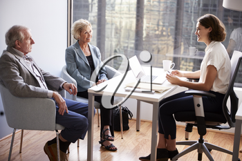 Smiling Senior Couple Meeting With Female Financial Advisor In Office