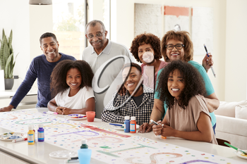 Three generation black family making a sign for surprise party smiling to camera,close up