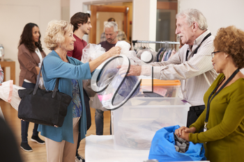 People Donating Clothing To Charity Collection In Community Center