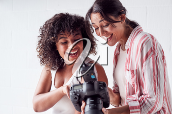 Smiling Female Photographer Holding Camera With Model In Studio Portrait Session