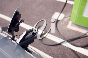 Close Up Of Power Cable Charging Electric Car Outdoors In Supermarket Car Park