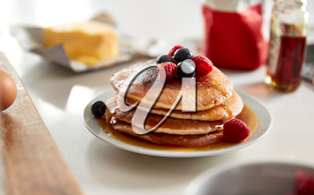 Stack Of Freshly Made Pancakes Or Crepes With Maple Syrup And Berries On Table For Pancake Day