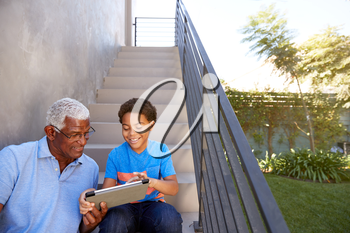 Grandfather With Grandson Sitting On Steps Outdoors At Home Using Digital Tablet