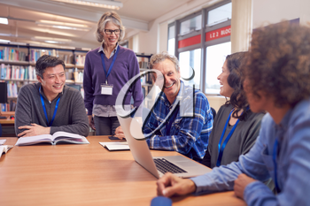 Teacher With Group Of Mature Adult Students In Class Sit Around Table And Work In College Library