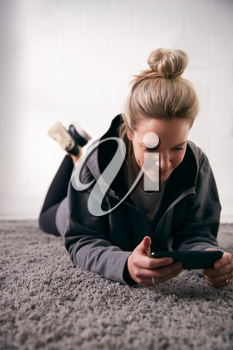 Woman Relaxing At Home Looking At Social Media And Text Messages On Mobile Phone Lying On Carpet