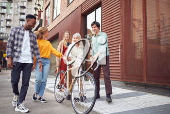 Group Of Multi-Cultural Friends Walking On City Street With Sustainable Bamboo Bicycle