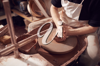 Close Up Of Female Potter Shaping Clay For Pot On Pottery Wheel In Ceramics Studio