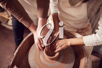 Male Teacher Helping Woman Sitting At Wheel In Pottery Class